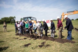 Scene of officials and representatives use shovels to break ground in Springdale