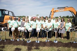 Group of staff members stand behind a row of shovels at groundbreaking site